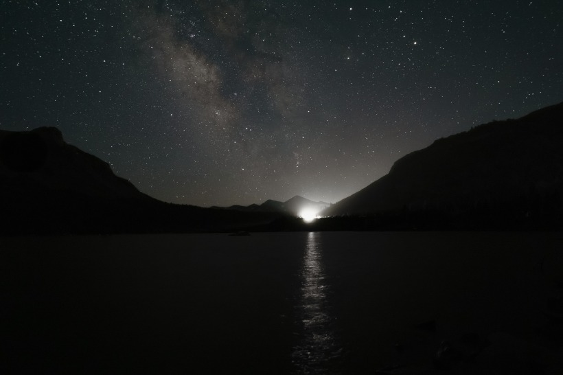 starry sky over a lake and mountains; a bright light just over the horizon.
