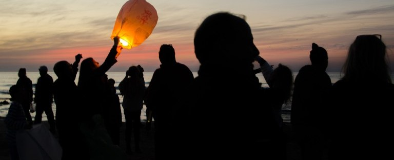 Sky Lantern by barakbro: a group of people standing on the beach at sunset; one holds a glowing paper lantern.