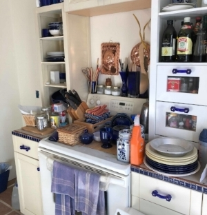 photo of my mother's kitchen: white cabinets with blue drawer pulls, blue counter tiles, dishes, jars, etc.