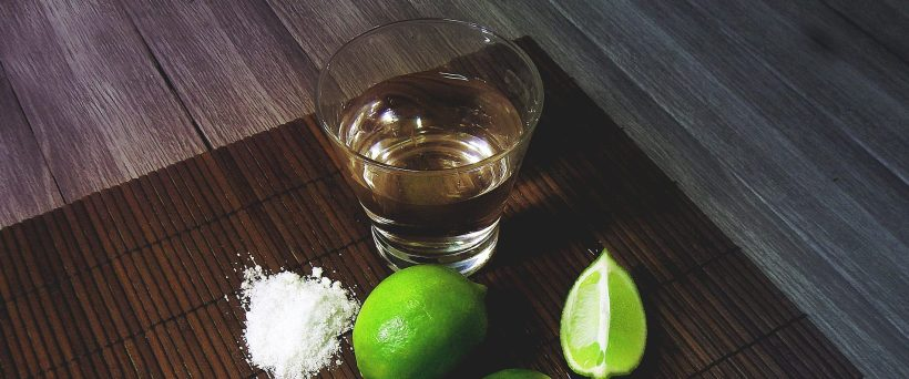 tequila in shot glass with salt and slices of limes