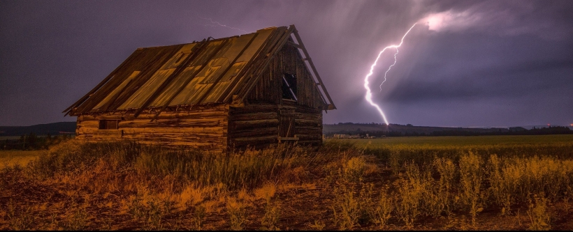 Photo of a barn. A lightning bolt strikes the fields beyond.