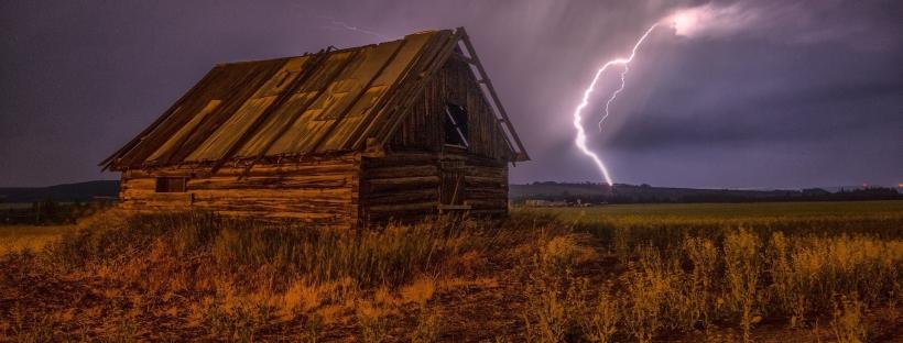 Photo of a barn. A lightning bolt strikes the fields beyond.