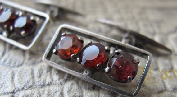 Pair of garnet cufflinks, each with three round garnets set in a rectangle.
