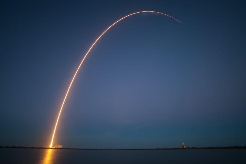 Orange rocket trail against deep blue evening sky
