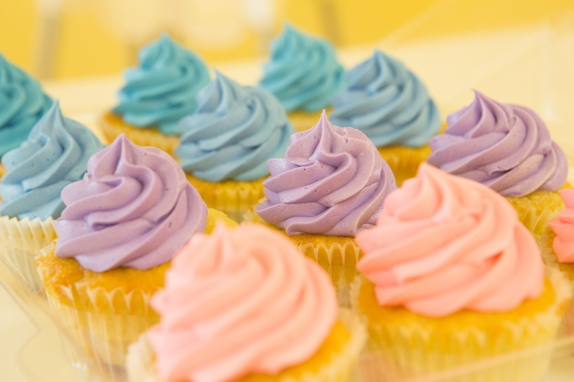 a set of vanilla cupcakes with pastel frosting