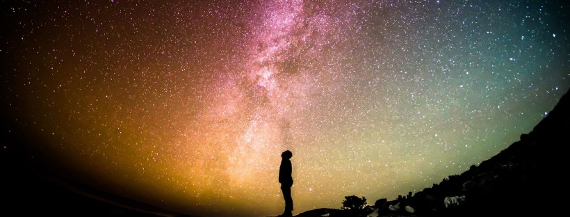 Photo: silhouette of a person looking up at the Milky Way
